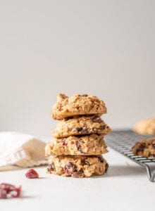 A stack of 4 cranberry orange oatmeal cookies sitting beside a cooling rack on a white surface.