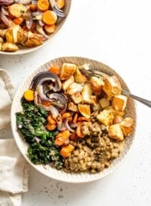 Roasted potatoes, lentils, carrots, onion and kale in a bowl topped with vegan miso gravy.