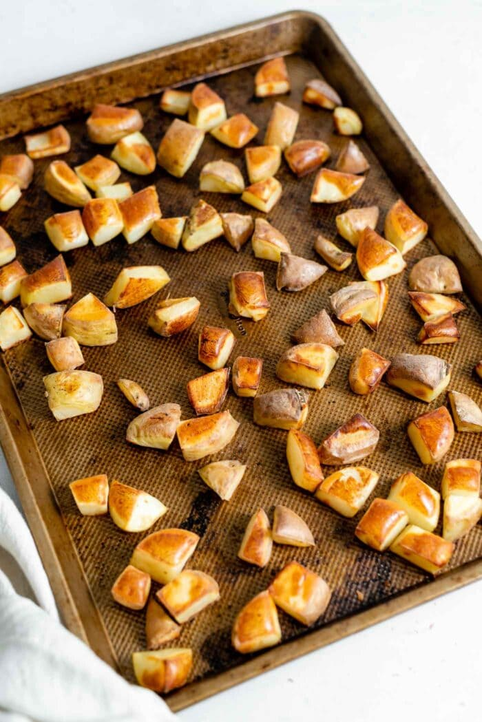 Roasted potatoes on a baking tray.