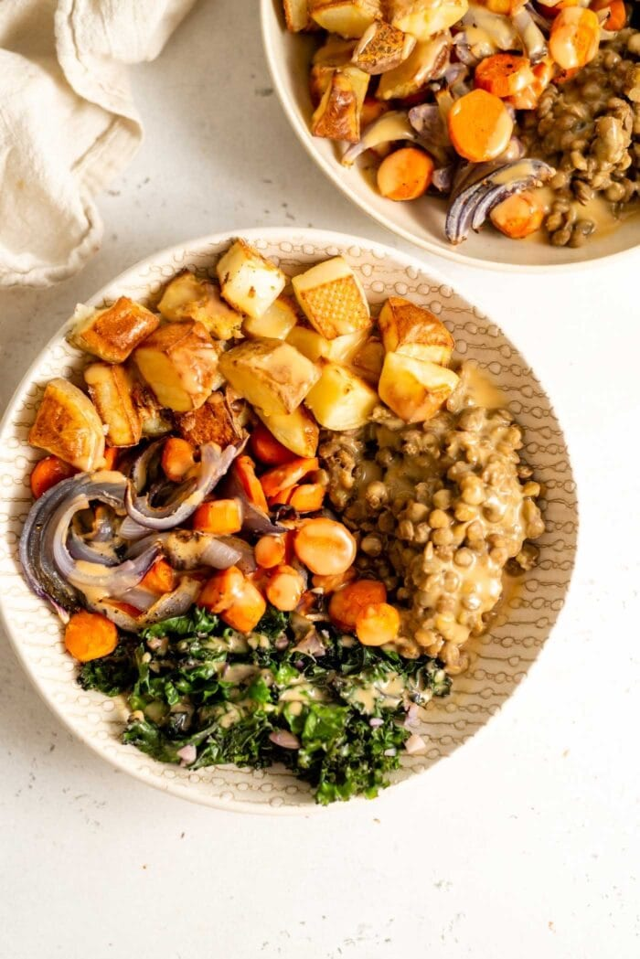Cooked lentils, potato, carrots, onion and kale in a bowl with miso gravy.