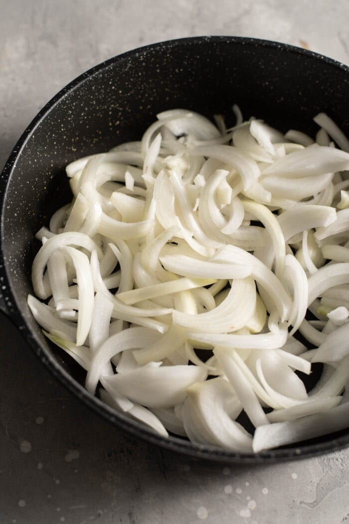 Chopped onions in a black skillet.