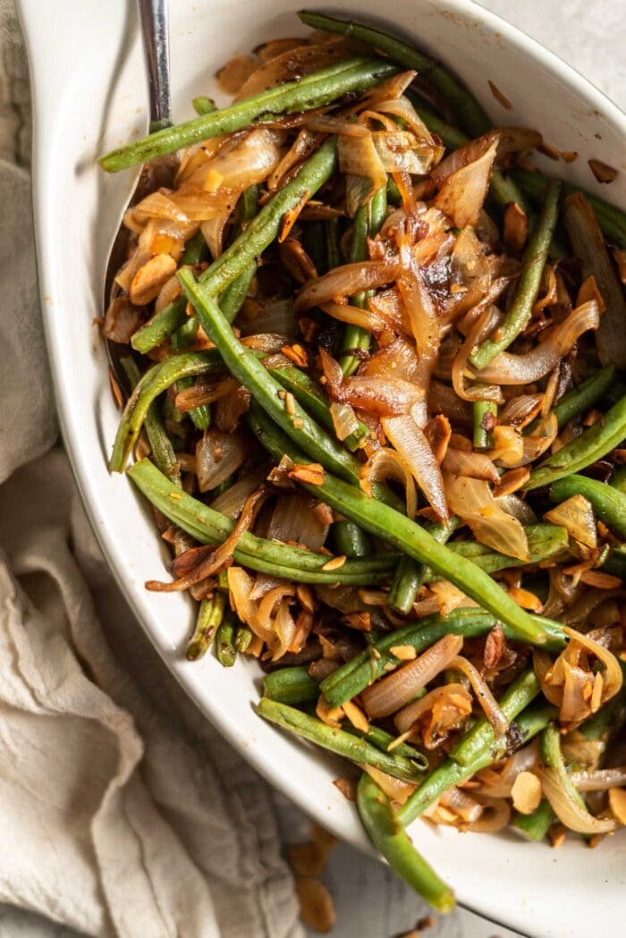 Sauteed green beans with onions, garlic and slivered almonds in a serving dish with a spoon.