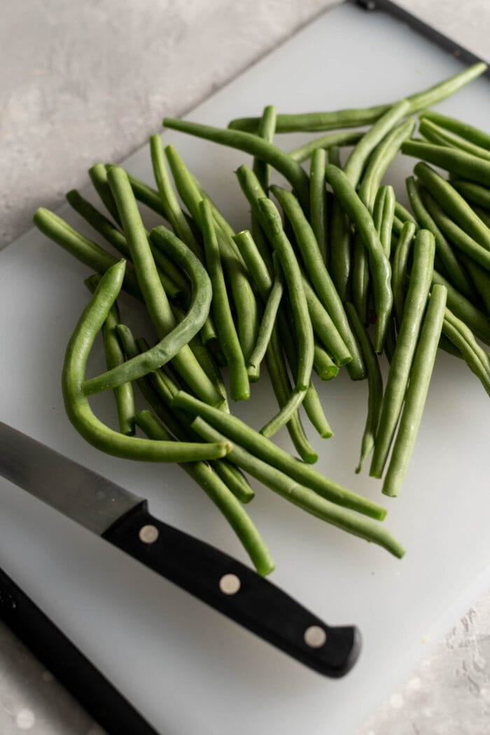 Trimmed green beans on a cutting board.
