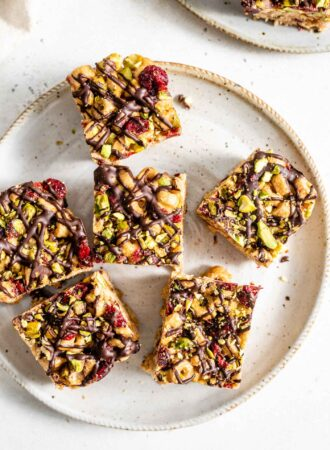 Five festive vegan cereal bars topped with pistachio and cranberries on a small plate.