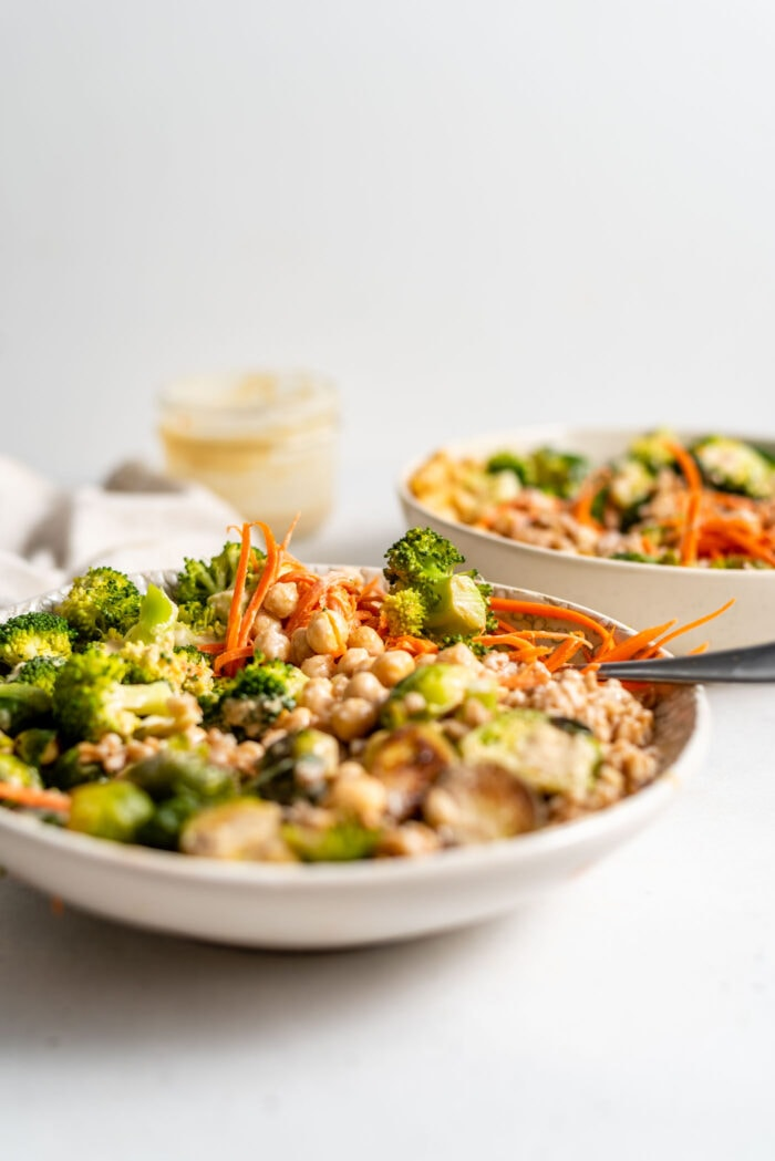 Roasted Brussels sprouts, broccoli, farro, chickpeas and carrot in a bowl.