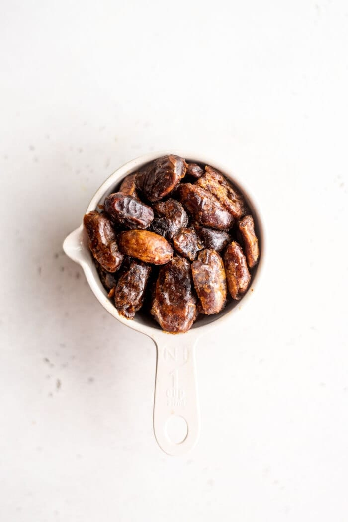 Pitted dates packed into a measuring cup.