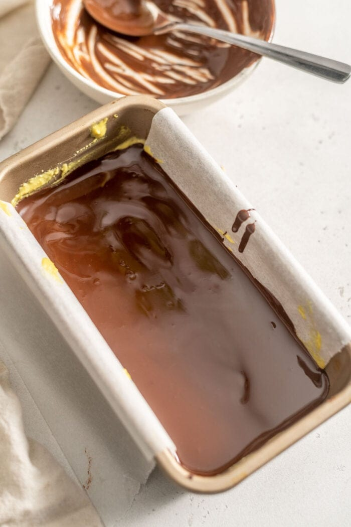 Melted chocolate in a loaf pan lined with parchment paper.