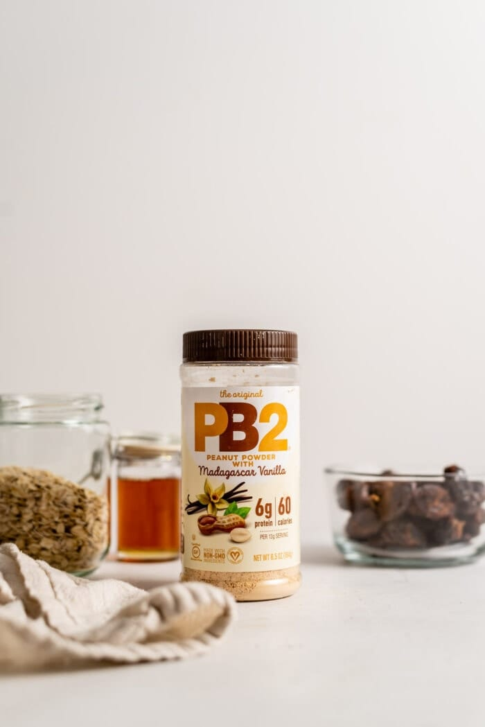 A jar of PB2 powdered peanut butter with maple syrup, dates and oats in the background.