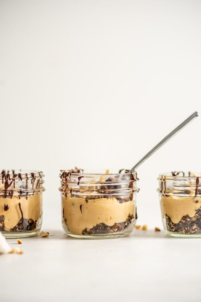 3 peanut butter mousse parfaits in small glass jars with a spoon scooping mousse out of one of them.