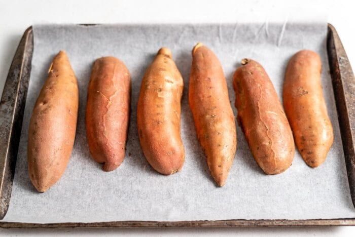 6 medium-sized sweet potato halves placed face down on a baking tray lined with parchment paper.