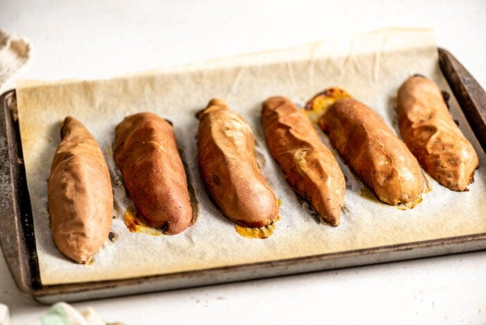6 baked sweet potato halves on baking tray.