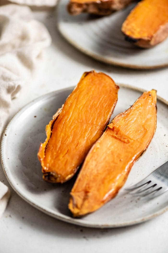 Two halves of a baked sweet potato on a plate with a fork.