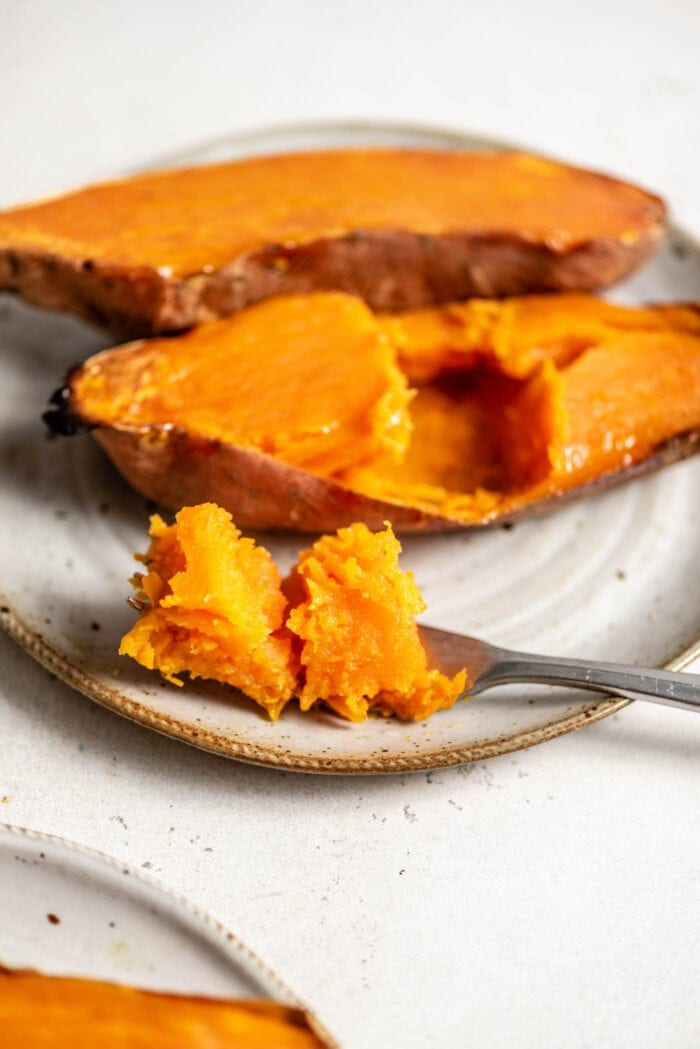 Two halves of a baked sweet potato on a plate with a fork topped with a chunk of sweet potato.