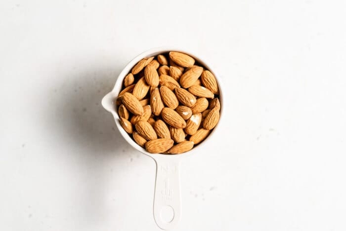 Raw almonds in a measuring cup.