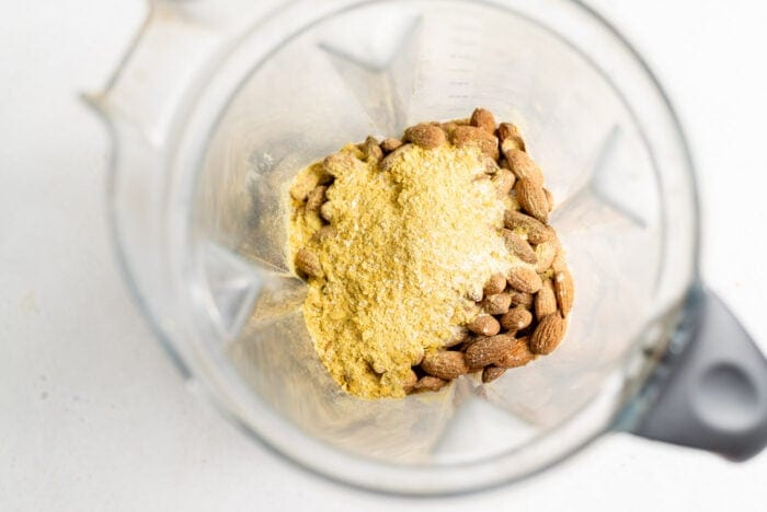 Nutritional yeast and raw almonds in a blender.