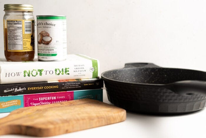 Cutting board, black frying pan and a stack of books with 2 cans of food top of them.