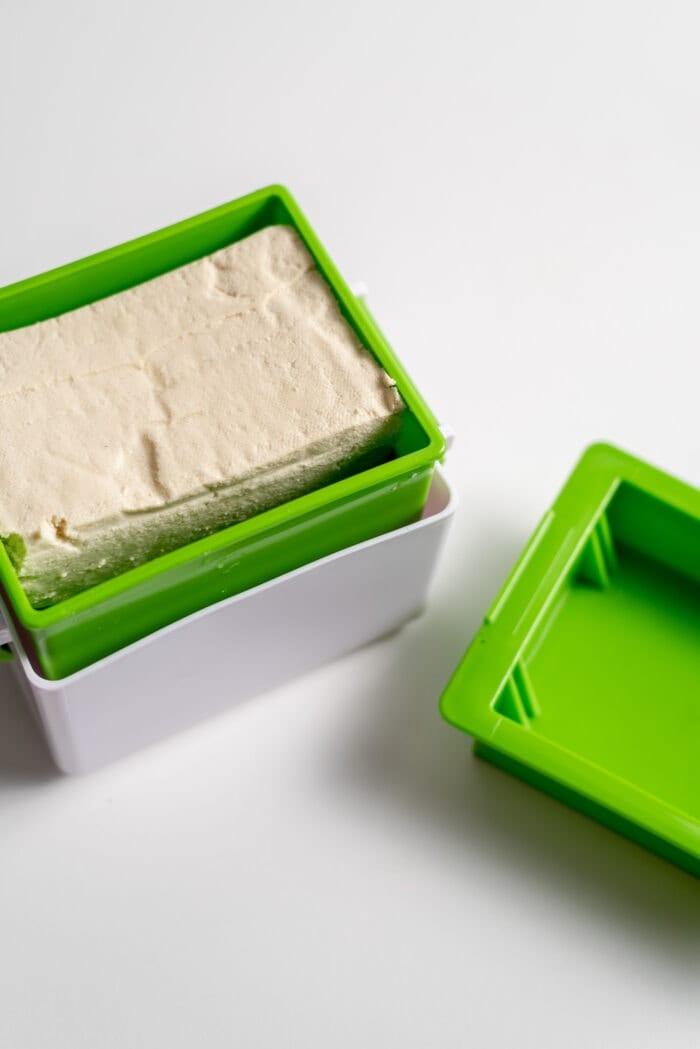 A block of tofu in a tofu press.