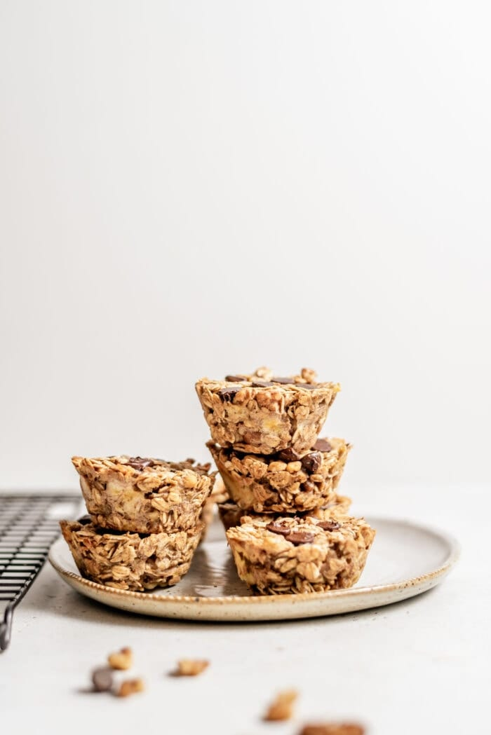Two stacks of baked oatmeal cups on a small plate beside a cooling rack.