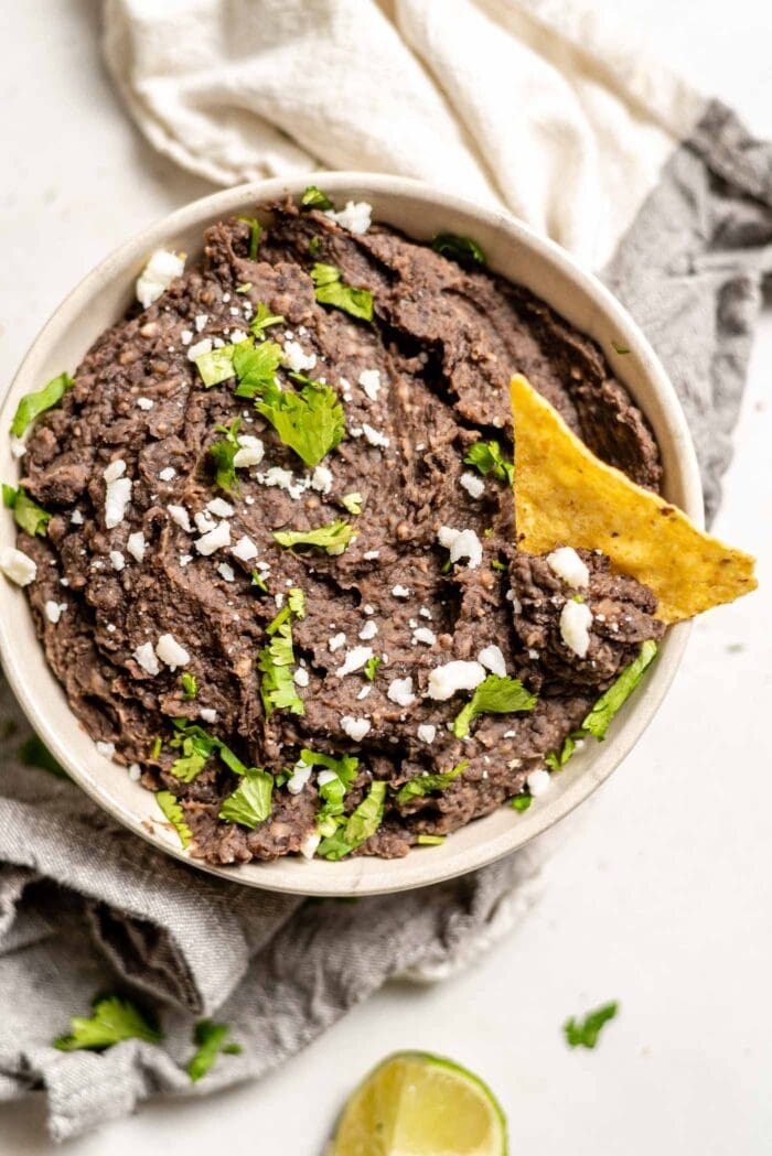 A bowl of vegan refried black beans with a chip in it topped with cheese and cilantro.