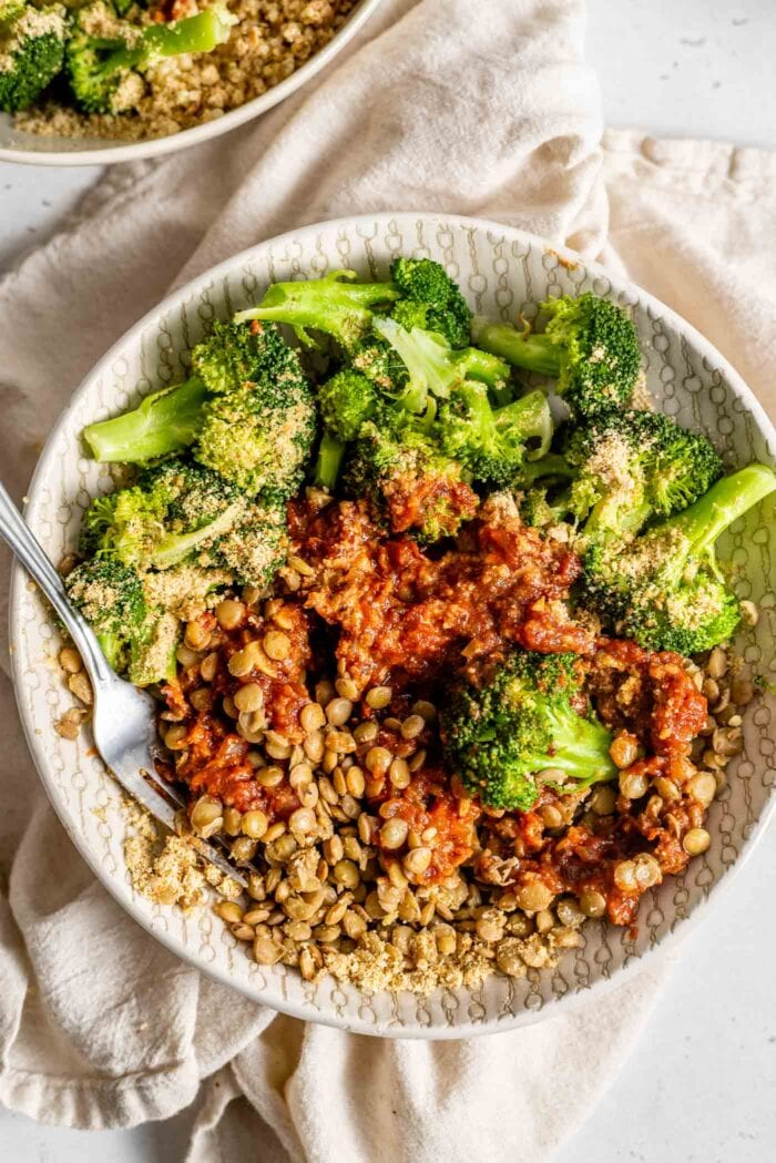 A bowl with steamed broccoli, vegan parmesan, lentils and marinara sauce.