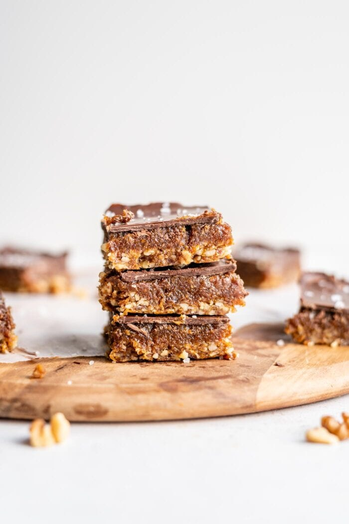 A stack of 3 chocolate caramel bars on a cutting board.