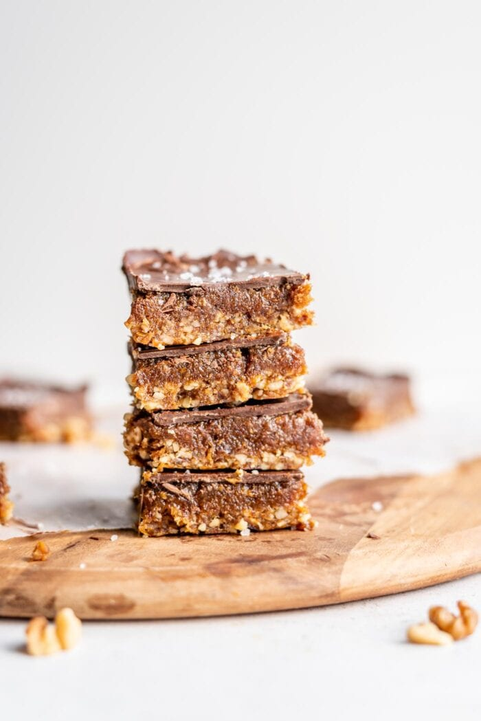 A stack of 4 chocolate caramel bars on a cutting board.