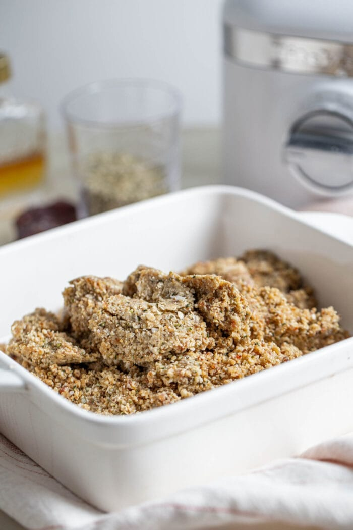 Crumbly dough with hemp seeds in a square baking dish.