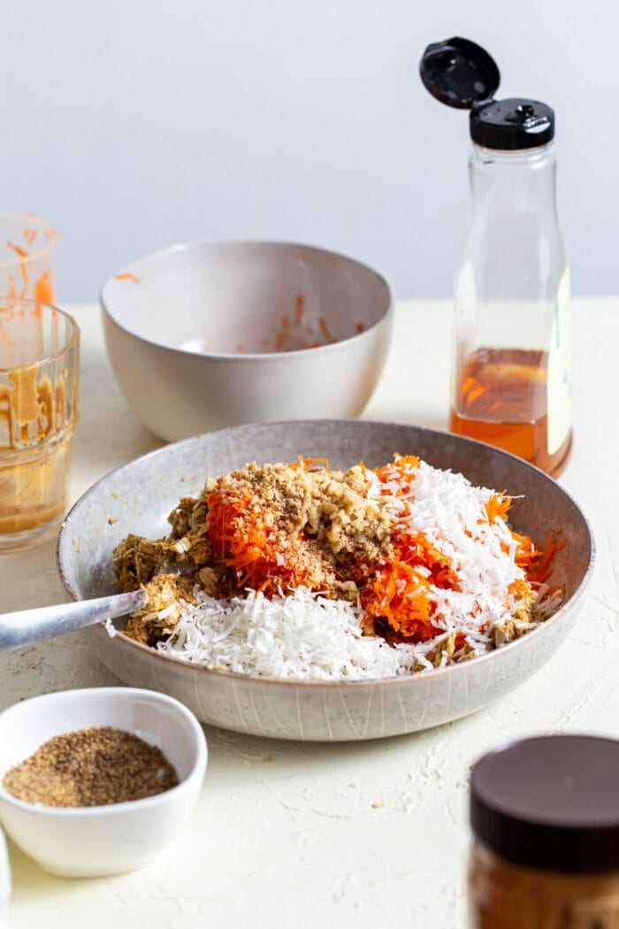 Carrots, walnuts and coconut in a mixing bowl.