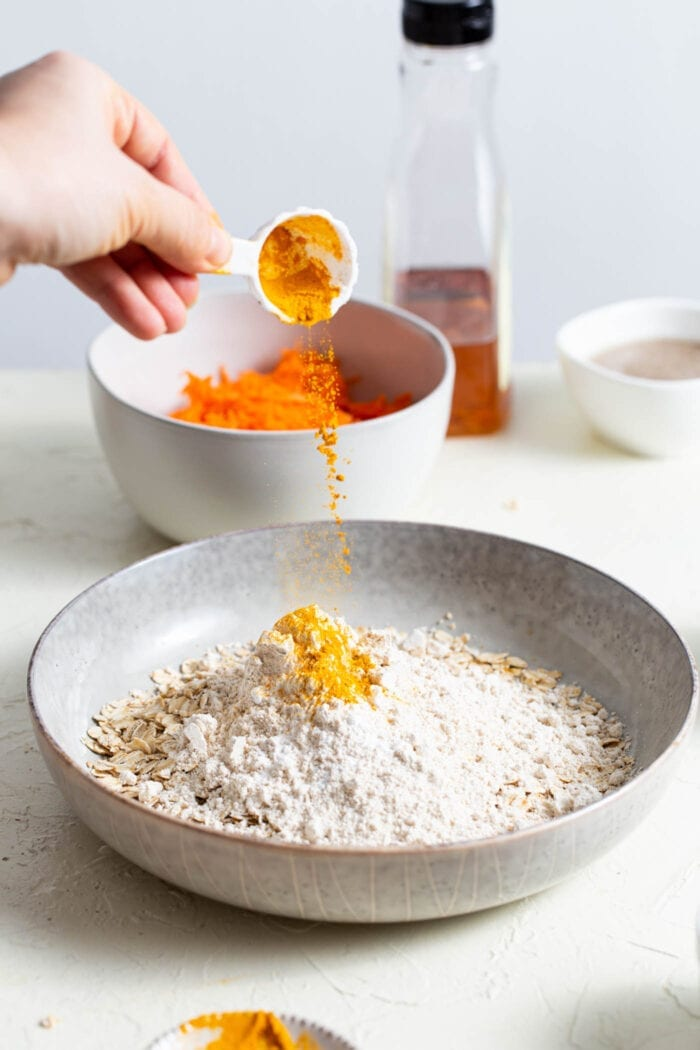 Adding ground turmeric to a mixing bowl with oats in it.