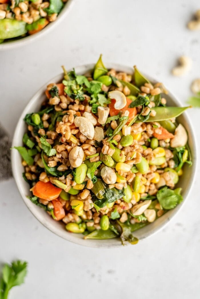A bowl of fried farro with carrot, snow peas, edamame and spinach.