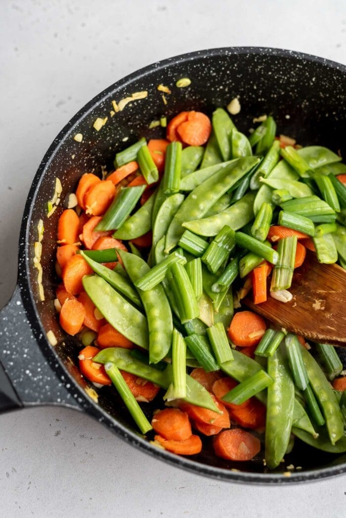 Carrots, green onions, snow peas and ginger in a skillet with a wooden spoon.
