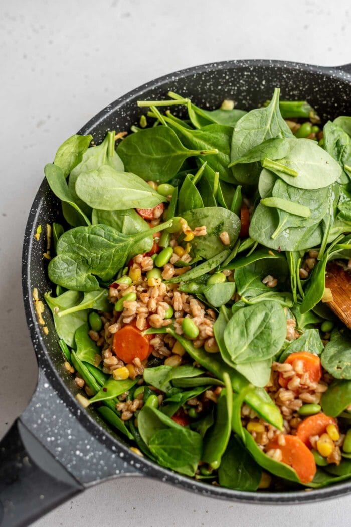 Fresh spinach in a skillet with farro and vegetables.