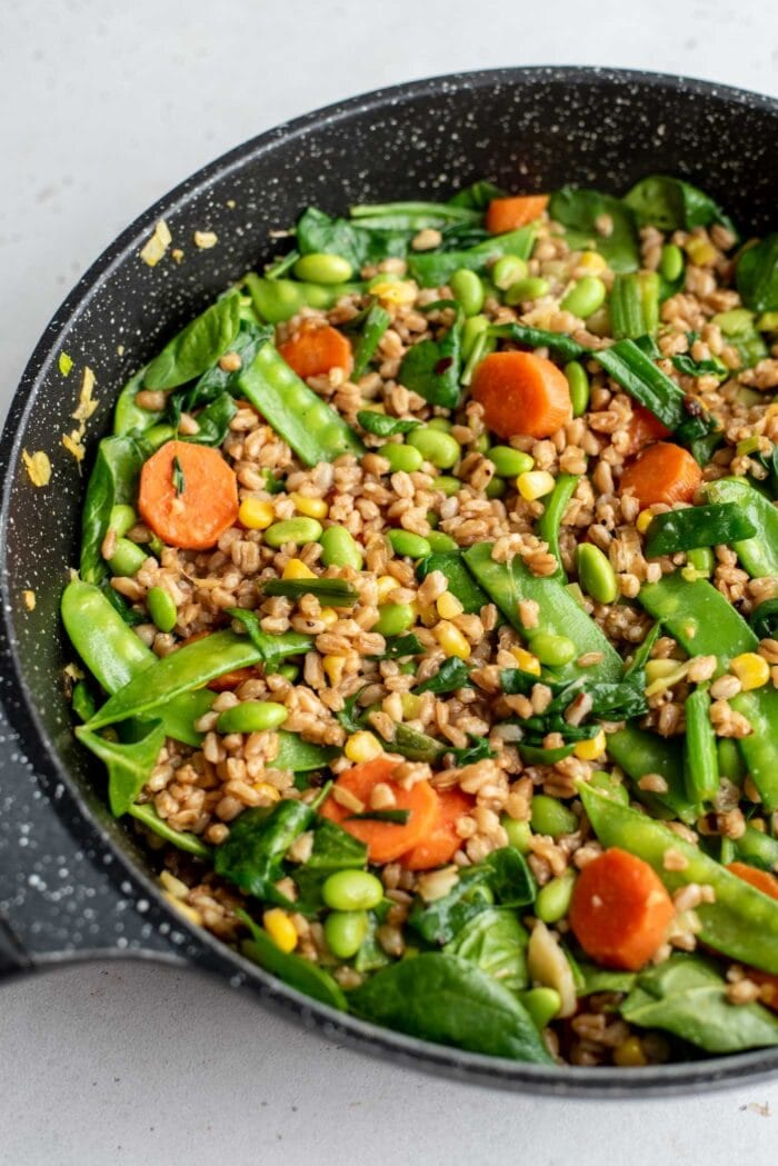Fried farro in a skillet with peas, edamame, carrot and spinach.