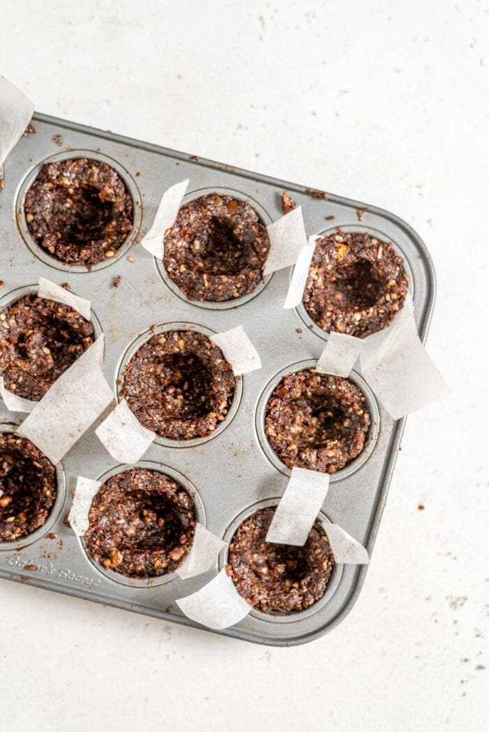 Unfilled chocolate tarts in a mini muffin tin.