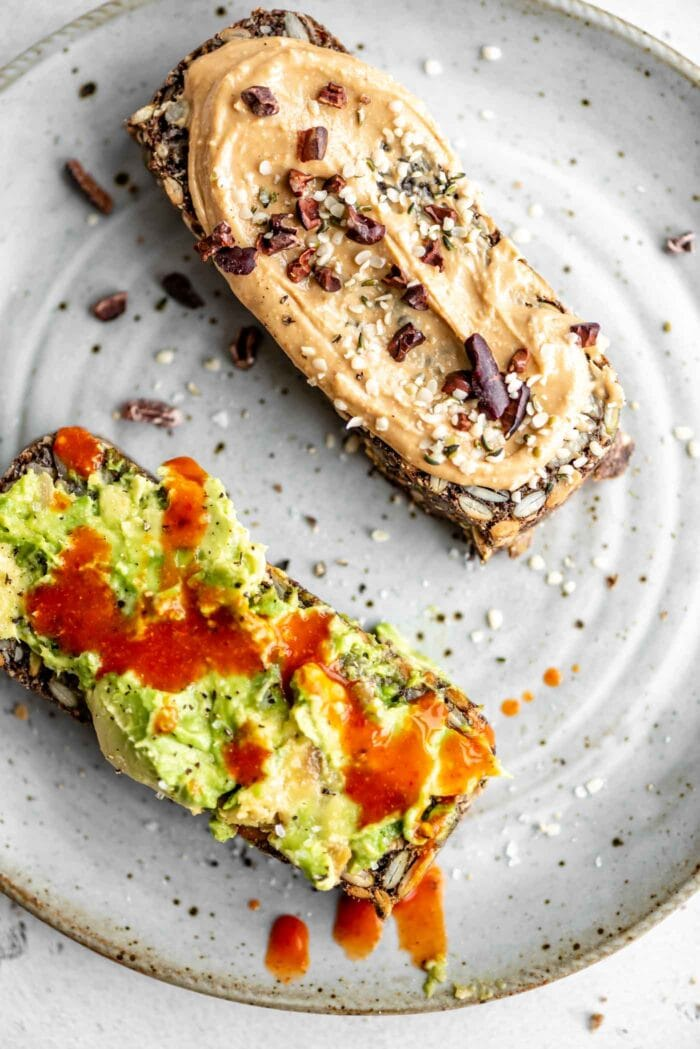 Two slices of seed loaf on a plate, one topped with avocado, one topped with peanut butter and cacao nibs.