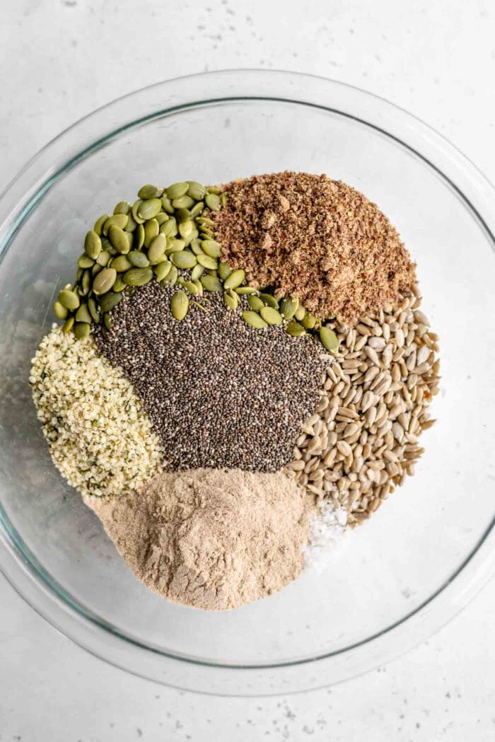 A mixture of raw seeds in a large mixing bowl.