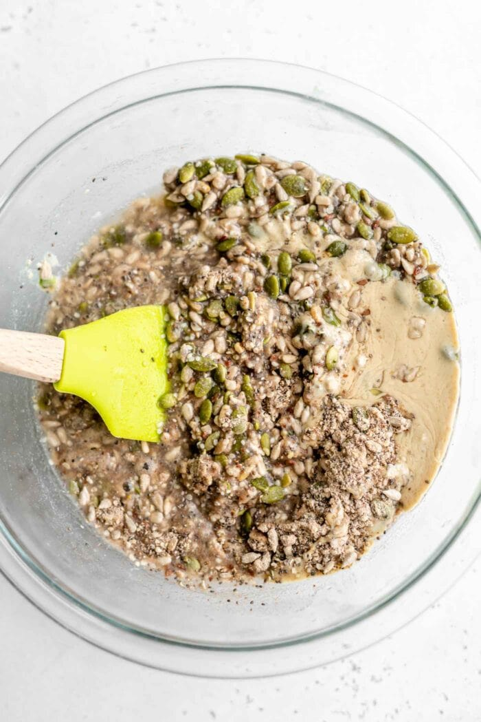 Seeds, water and tahini being mixed in a bowl.