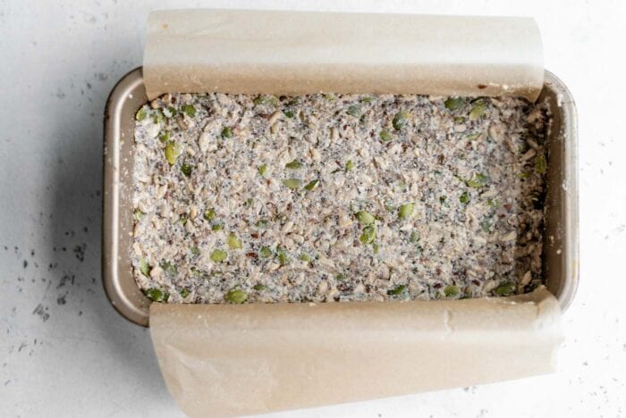 Raw seed bread in a loaf pan with parchment paper.