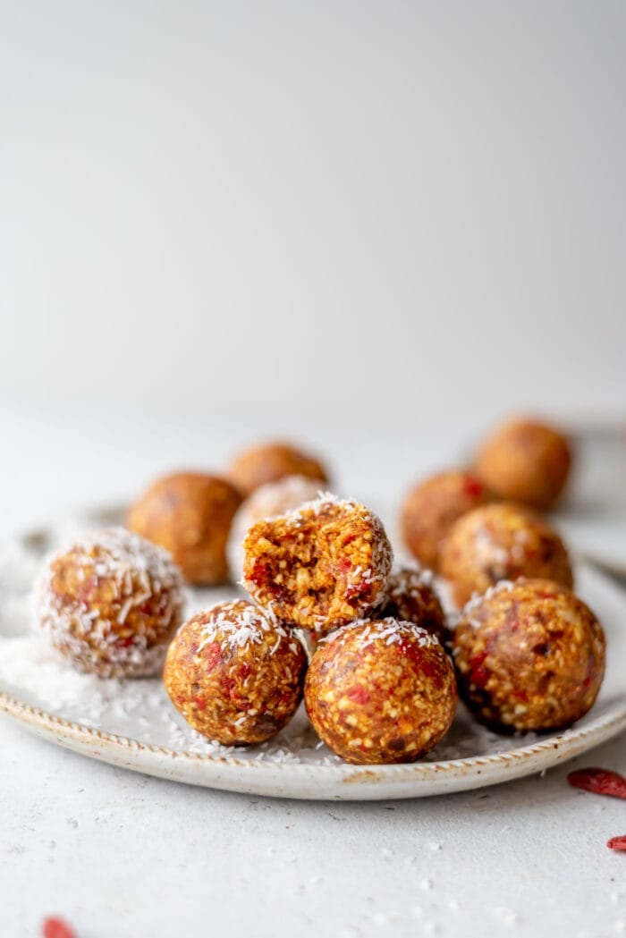 An orange energy ball with a bite taken out of it sitting on a plate with a few other balls.