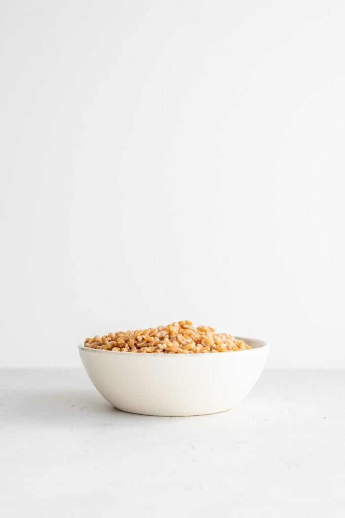A bowl of cooked farro sitting on a white surface.