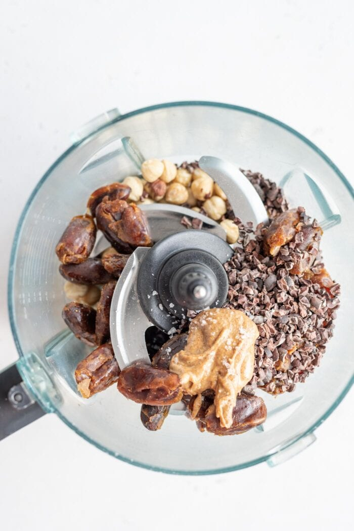 Dates, hazelnuts, cacao nibs and almond butter in a food processor.