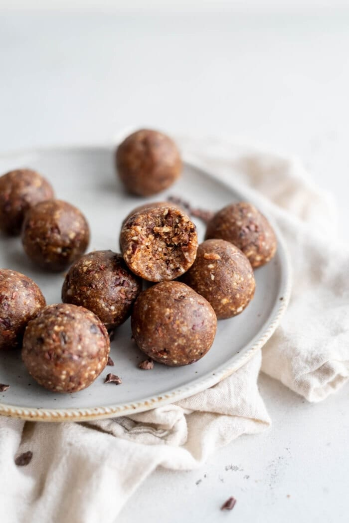 A hazelnut energy ball with a bite taken out of it sitting on a small plate.
