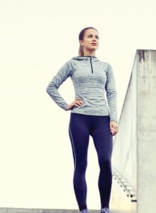 Fit woman in workout clothing standing outdoors on cement stairs.