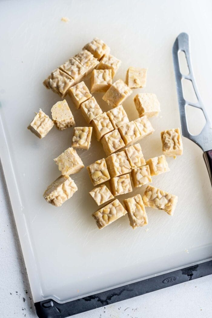 Cubed tempeh on a cutting board with a knife.