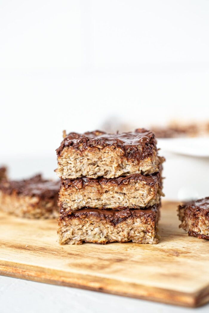 A stack of baked oatmeal bars topped with chocolate..