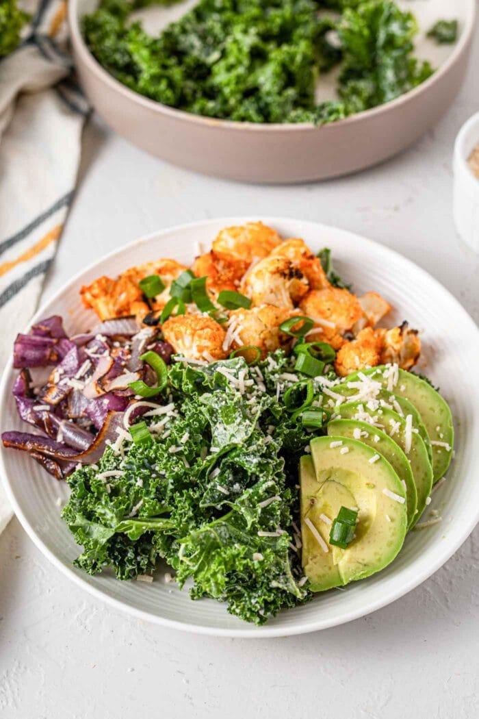 A bowl of kale, avocado, buffalo cauliflower, roasted onions and parmesan.