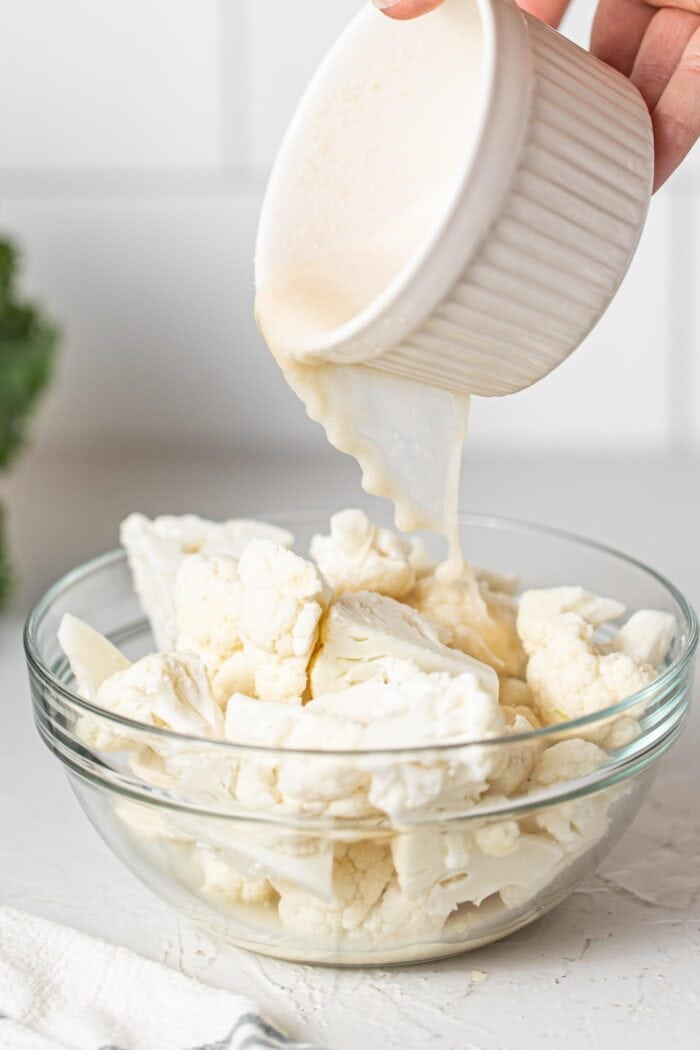 Dumping milk over chopped cauliflower in a glass bowl.