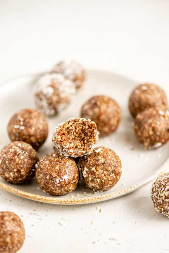 An energy ball on a plate with a bite taken out of it.
