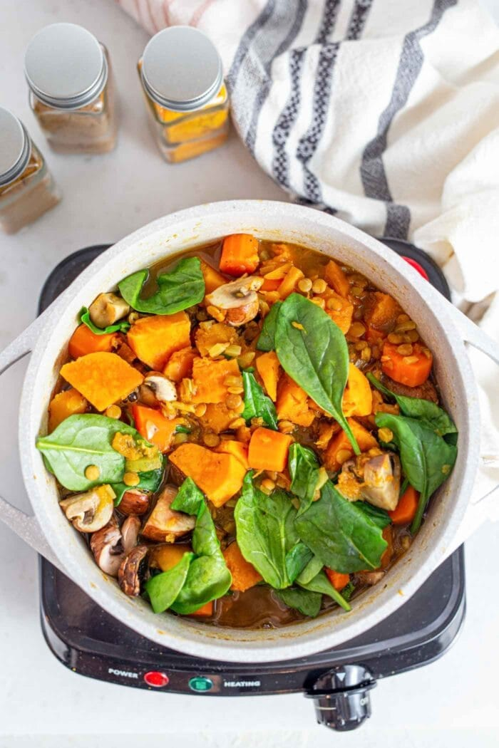 A spinach, mushroom and squash stew cooking in a large pot.