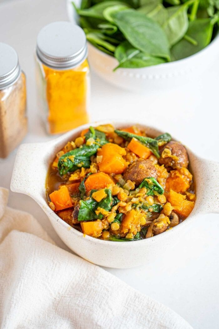 A bowl of butternut squash and lentil stew with mushrooms and spinach.